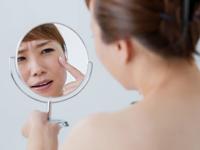 手鏡で顔を見ている女性